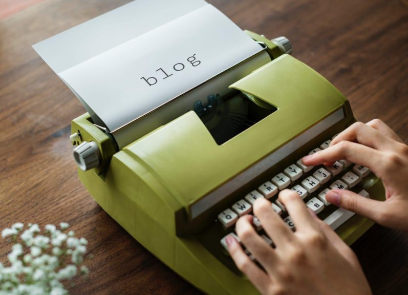 blog writing for money with a lime green typewriter